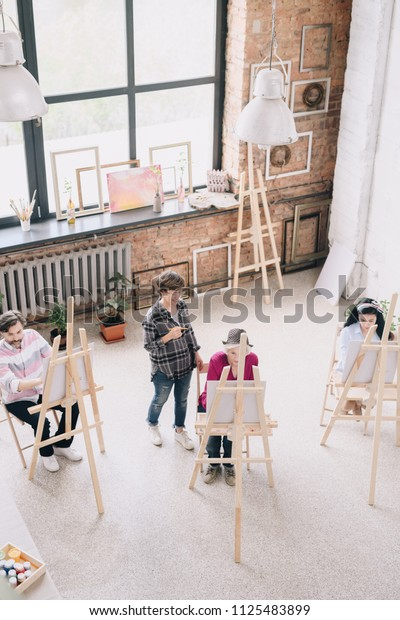 Above view  portrait of students  painting sitting by easels in art studio with female art teacher watching them in spacious sunlit loft space, copy space