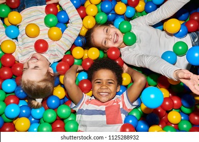 Above view portrait of three happy little kids in ball pit smiling at camera raising hands while having fun in children play center, shot with flash