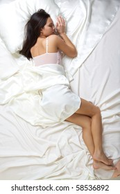 Above view of pretty female in peignoir sleeping on bed under silk sheets