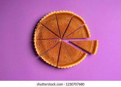 Above view of a pumpkin pie cut in slices with one piece separated, on a purple background. Minimalist food image. Thanksgiving traditional dessert.