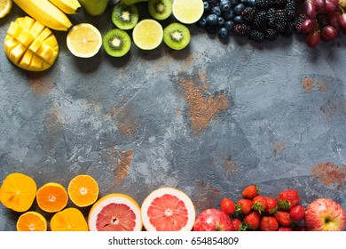 Above view of rainbow fruits on the grey concrete background, copy space for text, selective focus