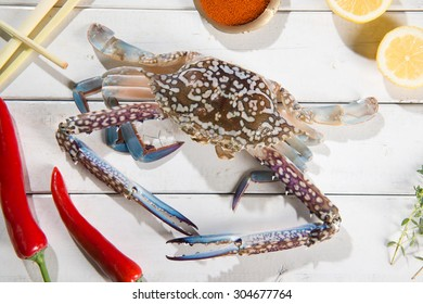Above view raw blue crab and ingredients ready to cook, on bright wooden background.