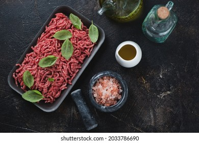 Above view of raw fresh beef mincemeat with seasonings over dark-brown stone background, horizontal shot with space