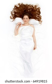 Above view of resting female under linen sheet with her long hair spread on pillow