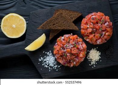 Above view of salmon tartar on a dark wooden background, studio shot