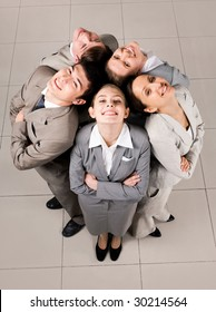 Above view of several business partners looking upwards at camera with their heads close to each other