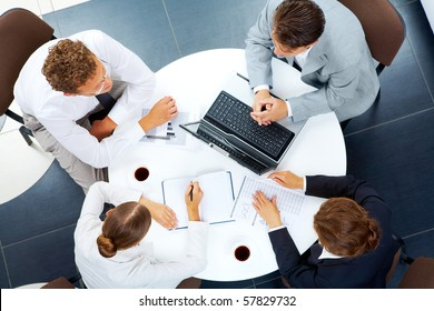 Above view of several business people planning work at round table