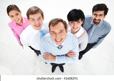 Above view of several successful partners looking at camera and smiling