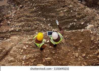 Above view shot of two industrial  workers wearing reflective jackets standing on mining worksite outdoors using digital tablet, copy space