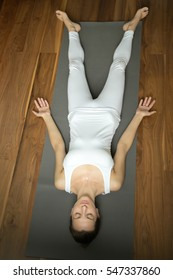 Above view of a sporty attractive woman practicing yoga, lying in Corpse, Dead Body exercise, relaxation Savasana pose, wearing white sportswear, indoor full length, home interior background