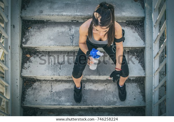 Above view of sporty girl with water bottle sitting on staircase outdoors.