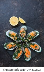 Above view of a stone slate tray with boiled kiwi mussels in parsley sauce, dark brown stone background with space