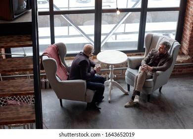 Above view of stylish middle-aged businessmen sitting in comfortable armchairs and drinking alcohol in lobby bar