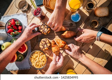 Above view of table full of food and people hands taking breakfast together like family or friends - sunny beautiful day and lifestyle concept for different ages men and women - coffee and fruit cakes