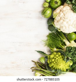Above view, table top green vegetables and fruits on the white wooden table, copy space for text on the left, horizontal, top view, selective focus
