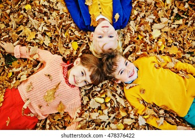Above view of three smiling children, two boys and girl, in bright clothes enjoying warm autumn day, playing in park and lying in pile of fallen leaves and looking at camera - Shutterstock ID 478376422