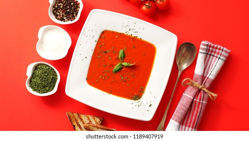 From above view of tomato soup with green leaves served in white plate with spoon and bowls full of spices on red background