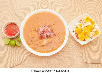 Above view of traditional Ecuadorian food called Encebollado, fish stew and ring onions inside, served with popcorn, chifles, lemon and red sauce inside of bowl
