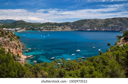 Above view of turquoise bay full of moored luxury yachts motorboats in the Mediterranean Sea, picturesque Cala Blanca Andratx, rocky mountains lush greenery Mallorca, Balearic Islands, Spain