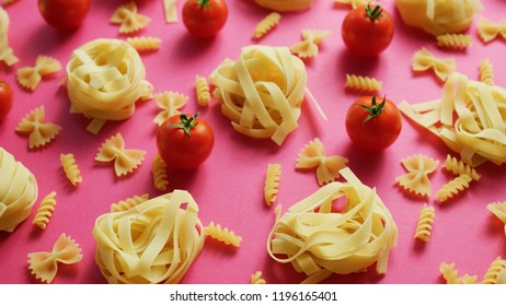 From above view of unprepared pasta of different type laid with fresh red tomatoes on pink background