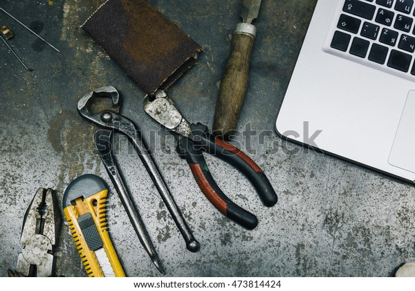 Above view of used hammer,pliers and chisel with laptop and smartphone on metal table