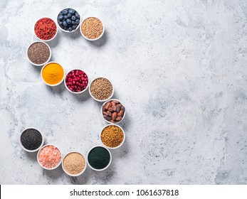 Above view of various superfoods in smal bowl in form S letter on gray background. Superfood as chia,spirulina,cocoa bean,goji, hemp, blueberry, quinoa, bee pollen,black sesame,turmeric. Top view