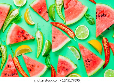 Above view at Watermelon and Chili pepper with lemons on green background