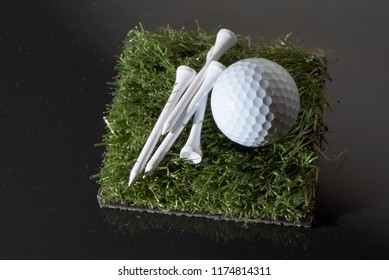From above view of white golf ball and fixtures laid on piece of ground covered with green grass on gray background