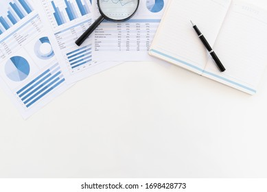 above view of white office desk with pan, notebook and business financial report of auditor desk. copy space.