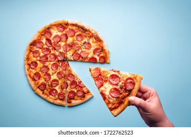 Above view with woman's hand taking a slice from a pepperoni pizza. Delicious homemade salami pizza top view. Fast food home-baked