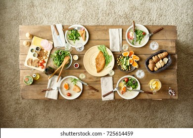 Above view of wooden dinner table with half-eaten dishes left on it, no people
