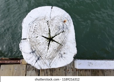 Above view of a wooden pole with heart and star shape on a boat jetty.