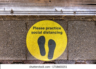 Above view for yellow warning sign to maintain social distance distancing during covid-19 coronavirus outbreak with footsteps on street