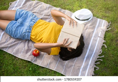 Above view of young black girl reading book on picnic blanket outside