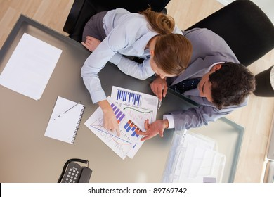 Above view of young consultant analyzing statistics with her client