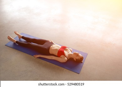 Above view of young woman working out in empty classroom, lying in Shavasana, resting after practice. Full length, top view