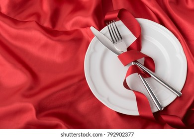 From above white plate and knife with fork on red fabric background.