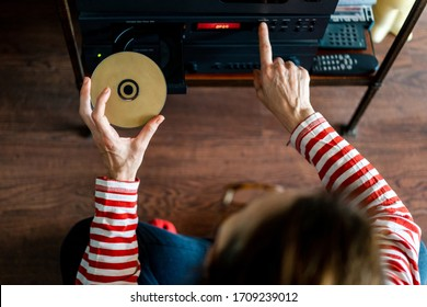 from above woman dressed in red striped t-shirt putting a compact disc or cd into a stereo in the interior of a house