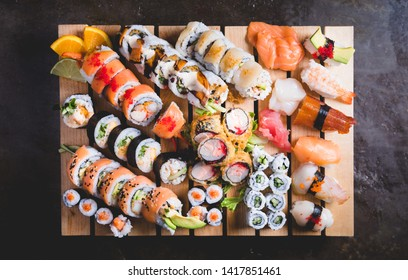 From above of wooden platter with big set of delicious Nigiri sushi and assorted Uramaki rolls with fresh fish and vegetables