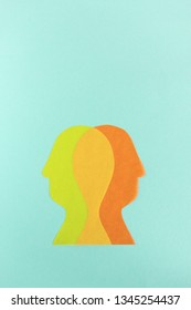 From above yellow and orange human head silhouettes on turquoise background