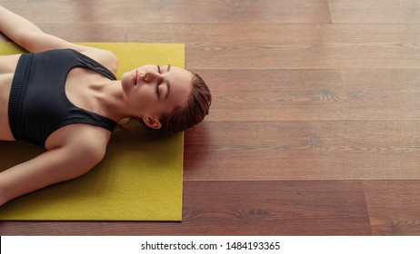 From above young lady with closed eyes lying in corpse pose on yoga mat on wooden floor in gym