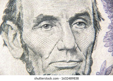 Abraham Abe Lincoln face on 5 dollar bill close up. Portrait of famous US president on dollar banknote. Macro view of USA paper money. Detail of new currency note.