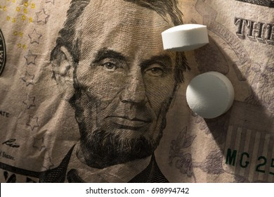 Abraham Lincoln on American dollar bill with pills on top symbolizing health care costs and victory against disease, investment risk and budget constraints.