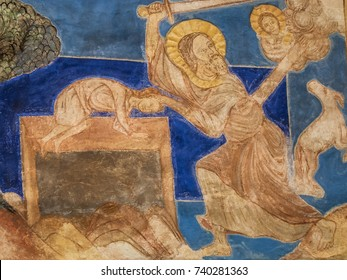 Abraham scarifies his son Isaac on the altar and is about to kill him, but is prevented by an angel. A romanesque wall-painting in Bjaresjo church, Sweden, November 6, 2009