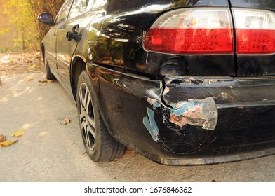 Abrasions on the rear bumper of black cars after an accident.