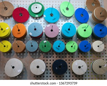 abrasive circles for industrial equipment power tools for grinding, cutting or polishing at DIY hardware store warehouse. different colors for various grain