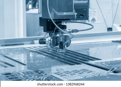 The abrasive water jet  machine in the light blue scene. The metal cutting by abrasive water jet cutting method.