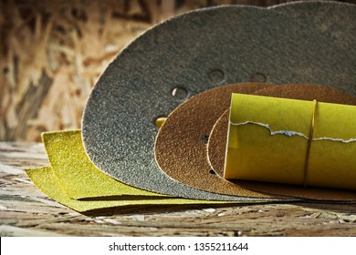 abrasives round square and rolled  sheets of sandpaper on plywood background