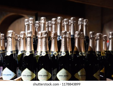 Abrau-Durso, Russia - August 22, 2018: Bottles of champagne on the counter. Shelves with wine and champagne in the store winery. Counter at the winery.