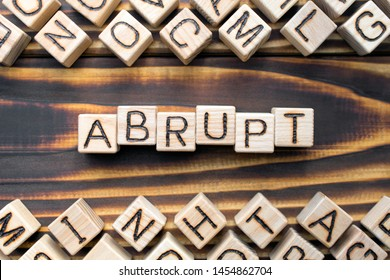 abrupt wooden cubes with letters, rude and unfriendly concept, around the cubes random letters, top view on wooden background